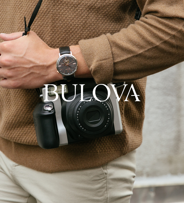 Person holding a camera with a watch on their wrist